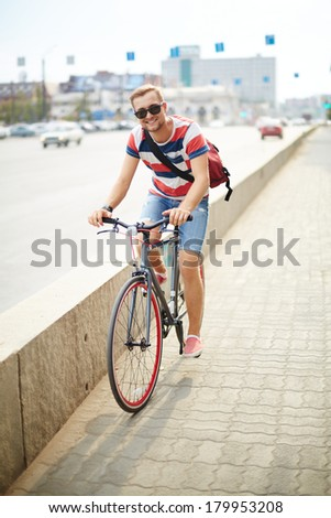 Portrait of happy guy riding bicycle in the city - stock photo