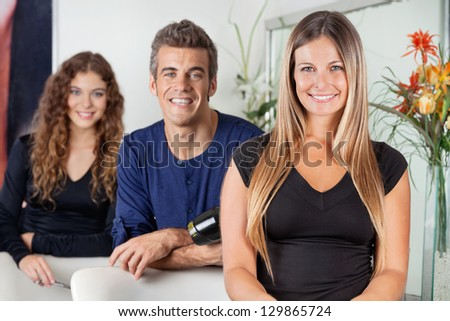 Portrait of happy hairdressers standing together in beauty parlor - stock photo