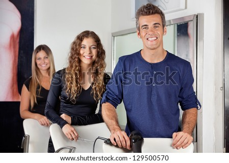 Portrait of happy hairdressers with hairdryer and scissors in salon