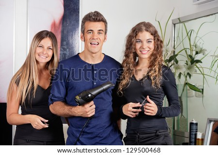 Portrait of happy hairstyling team with dryer and scissors standing together at beauty parlor - stock photo