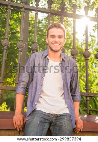 Portrait of happy handsome guy standing near the fence at city park. - stock photo