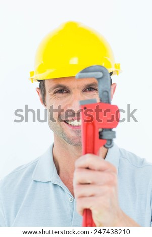 Portrait of happy handyman holding monkey wrench against white background