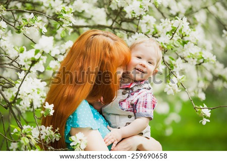 Portrait of happy happy mother ands son in spring garden. They playing and laughing. Blooming apple-trees. Family concept.  - stock photo