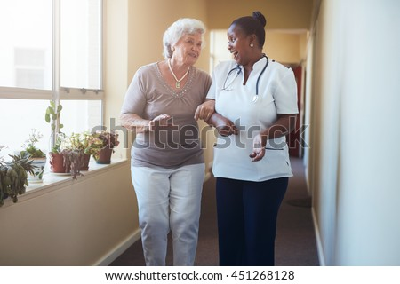 Portrait of happy healthcare worker walking and talking with senior woman. Elder woman gets help from nurse for a walk through nursing home. - stock photo