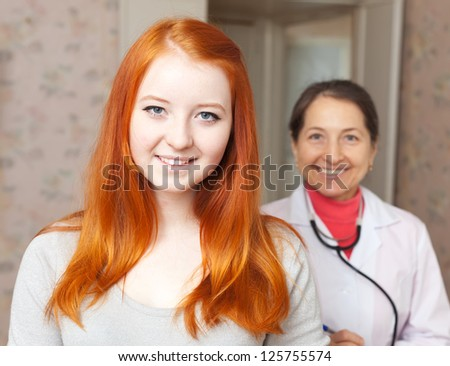 Portrait of happy healthy teenager patient against doctor - stock photo