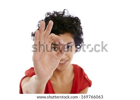 Portrait of happy hispanic girl doing ok sign with hand, smiling at camera