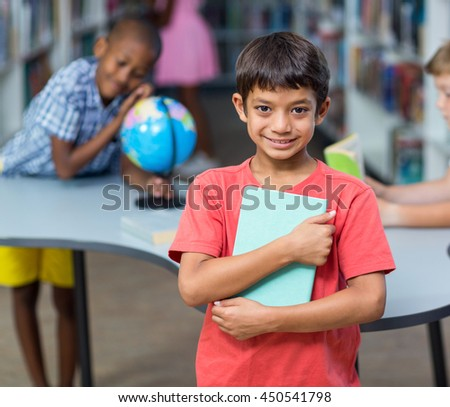 Portrait of happy holding books against classmates in library