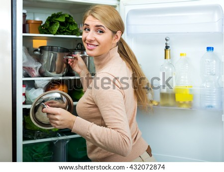 Portrait of happy housewife near filled fridge indoors - stock photo