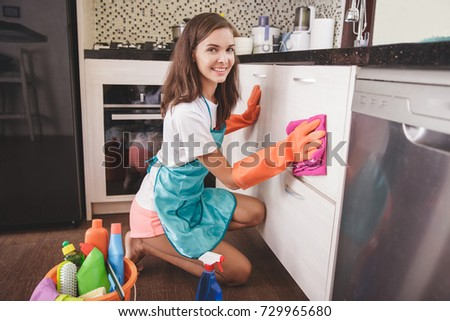 portrait of happy housewife smiling while cleaning kitchenware