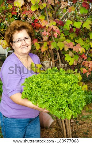 Portrait of happy housewife with raw fresh vegetable in garden