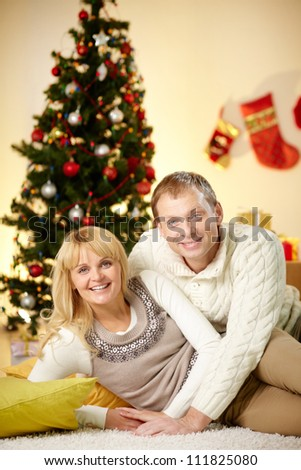 Portrait of happy husband and wife relaxing at home on Christmas day