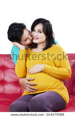 Portrait of happy husband kissing his wife on the sofa, isolated on white background - stock photo