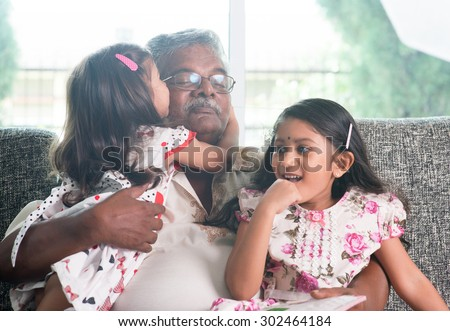 Portrait of happy Indian family at home. Grandchild kissing grandparent. Grandfather and granddaughters. Asian people living lifestyle. - stock photo