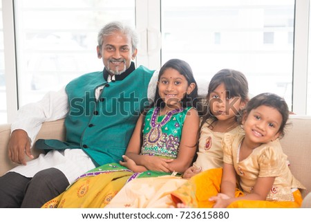 Portrait of happy Indian family in traditional clothes at home, smile at camera. Asian father and children indoors lifestyle.