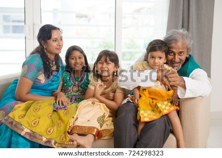 Portrait of happy Indian family sitting on couch at home. Asian people indoors lifestyle.