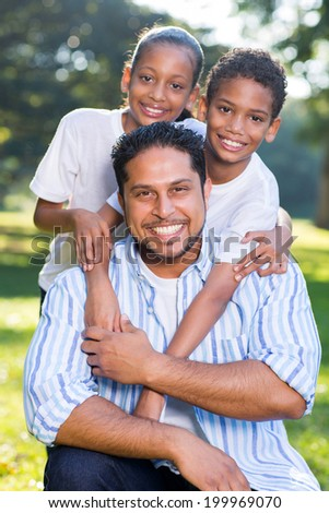 portrait of happy indian father and kids outdoors - stock photo