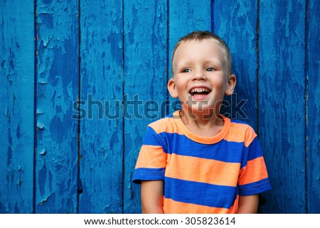 Portrait of happy joyful beautiful little boy against the old textured blue wall - stock photo