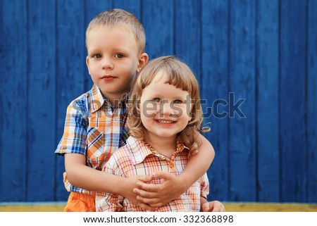 Portrait of happy joyful beautiful little boy and girl against the old textured blue wall - stock photo