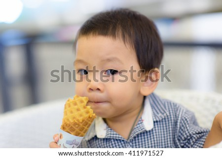 Portrait of happy kid biting ice-cream cone