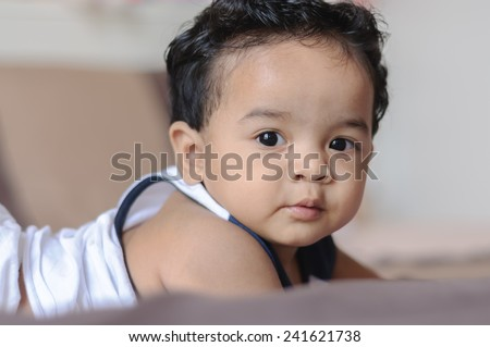 Portrait of happy kid on the bed   - stock photo