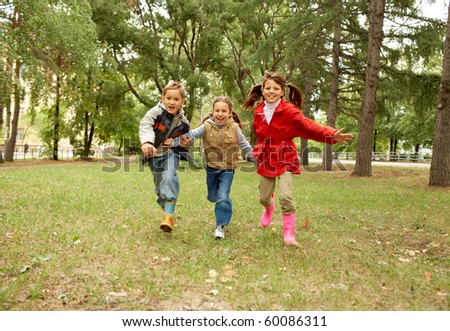 Portrait of happy kids running together in autumnal park - stock photo