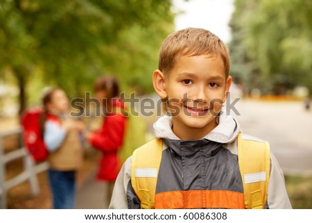 Portrait of happy lad with rucksack on back looking at camera outside - stock photo