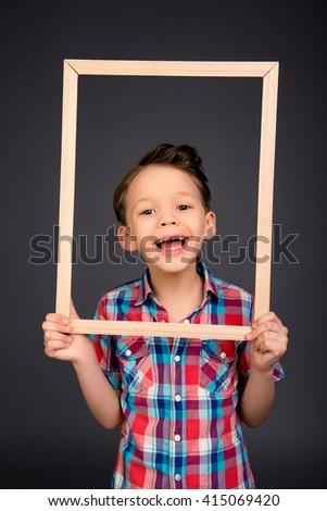 Portrait of happy laughing little boy with wooden frame - stock photo