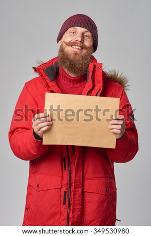 Portrait of happy laughing man wearing red winter Alaska jacket showing big envelope - banner with copy space for text, looking at camera - stock photo