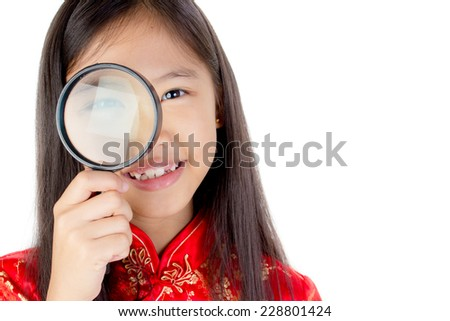 Portrait of happy little Asian child with magnifying glass - stock photo