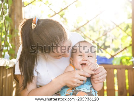 Portrait of happy little asian mom kissing son outdoors on green summer garden with fresh grass background Cute latin hispanic mother embracing baby boy looking at camera - stock photo