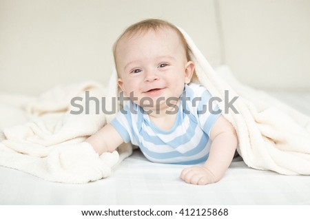 Portrait of happy little baby crawling on bed under blanket - stock photo