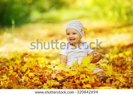 Portrait of happy little baby girl playing with yellow autumn leafs at natural outdoors park background. - stock photo