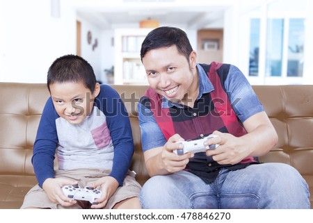 Portrait of happy little boy and his father playing video games together at home