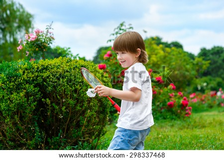 Portrait of happy little boy holding badminton racket and shuttlecock while standing on green grass - stock photo