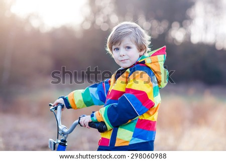 Portrait of happy little boy on bicycle, outdoors. Active leisure with children in winter, spring or autumn. - stock photo