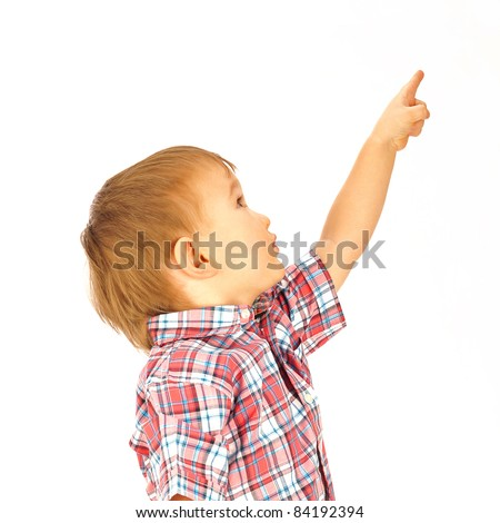 Portrait of happy little boy over white background looking away and pointing up - stock photo