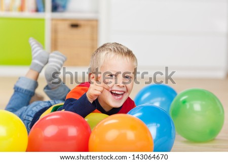 Portrait of happy little boy pointing while lying with colorful balloons on floor - stock photo