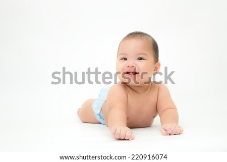 portrait of happy little boy who is smiling and lying on stomach, 5 months old asian baby boy - stock photo