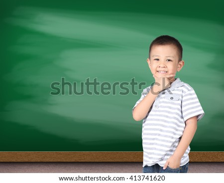 Portrait of happy little boy with green chalk board