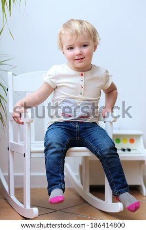 Portrait of happy little child, adorable toddler girl with curly blonde hair in casual clothes posing indoors sitting on a white rocking chair - stock photo