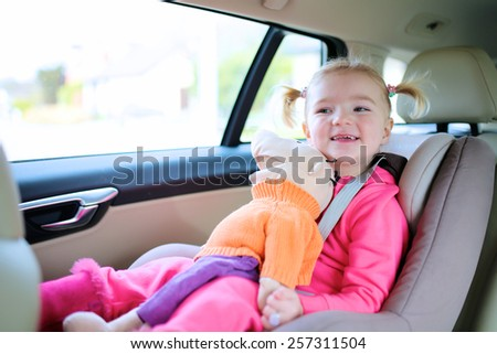 Portrait of happy little child, cute blonde toddler girl sitting comfortable in car seat with safety belts enjoying ride in the auto on family weekend trip - stock photo