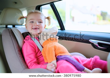 Portrait of happy little child, cute blonde toddler girl sitting comfortable in car seat with safety belts enjoying ride in the auto on family weekend trip