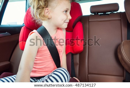 Portrait of happy little child girl sitting comfortable in car seat with safety belts enjoying ride in the auto on family weekend trip
