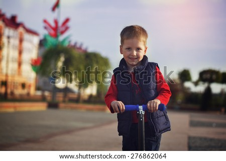Portrait of happy little child,  learning to ride and balance on push scooter on the street in the countryside - stock photo