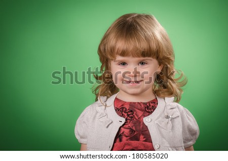 Portrait of happy little girl against green background