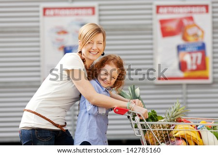 Portrait of happy little girl and mother pushing shopping cart together outdoors - stock photo