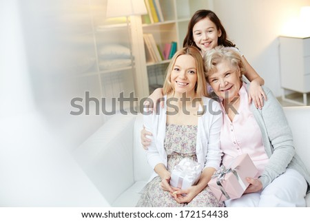 Portrait of happy little girl, her mother and grandmother with giftboxes looking at camera at home - stock photo