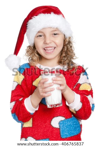 Portrait of happy little girl in pajamas and santa hat with glass of milk isolated on white background