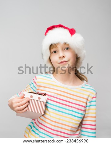 Portrait of happy little girl in santa hat with gift box over  - stock photo