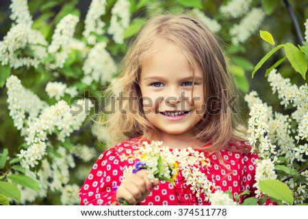 Portrait of happy little girl in spring flowers - stock photo